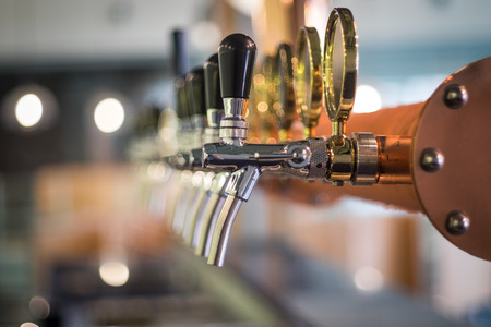 Row of draft beer tab on the top of counter bar in closeup view, time of celebration, selective focus.