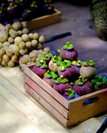 The pile of mangosteen and wollongong are in a small wooden crate. Put on a light yellow surface Inside the outdoor market, selective focus. Stock Photo