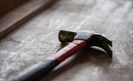 Old vintage hammer on the carpenter work table, selective soft focus.