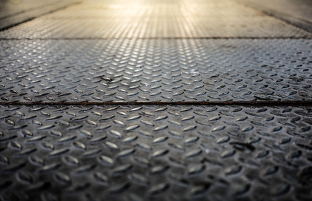 Close up of old checker plate steel floor with flare light effect, through the use of moderate, selective soft focus. Stock Photo