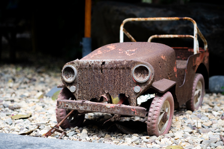 Old vintage car toy with rusty surface parking on the gravel stone floor, selective focus. Stock Photo