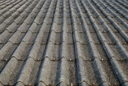 Old gray concrete roof tiles with dirt stains all over the sheet has been used for a long time, one point perspective view.
