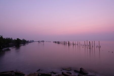 The wooden poles were lined up in a row in the sea. Appears as a reflection on the water surface During the sunrise on a new morning.