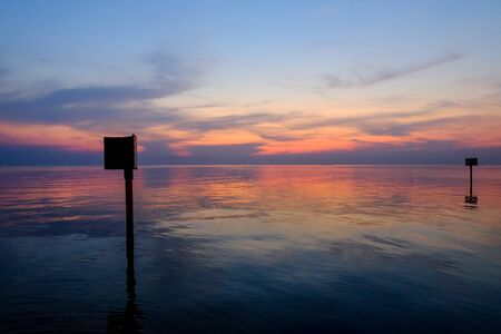 Sunset scene with warning marking steel pole in the sea, twilight time. Stock Photo