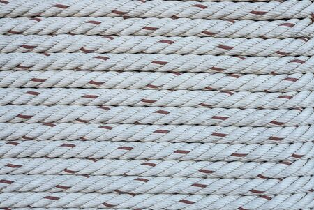 The horizontal pattern of the rope tied on a wooden port pole in close up view.
