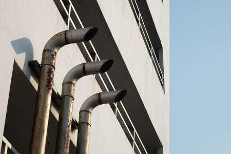 Three pipe ventilation ducts For venting smoke outside the building, rusty surface surrounding with sunlight and blue sky background. Reklamní fotografie
