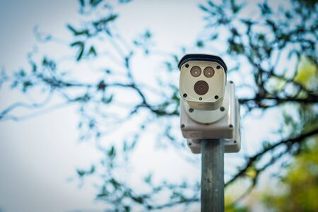 cctv security camera installed a top of round metal pole for surveillance nearby with natural background.
