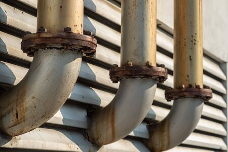Connection point of the  three pipe ventilation ducts For venting smoke outside the building, rusty surface surrounding with sunlight and aluminium louver window background.