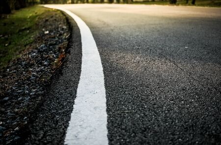 White curve road line on the asphalt floor with soft sun light effect and selective focus, concept of business or travel.