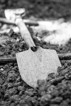 Shovels which are partially covered on the ground mixing with other tools, selective focus.