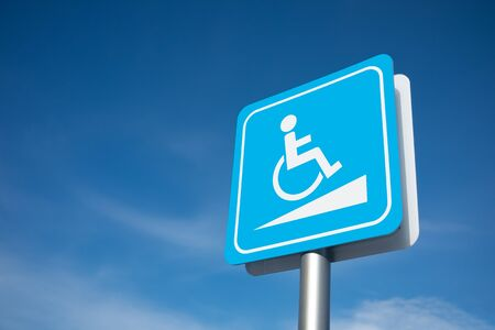 Disabled parking signage on the pole in blue and white color with cloudy blue sky