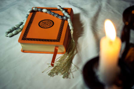 Quran religious book and candle