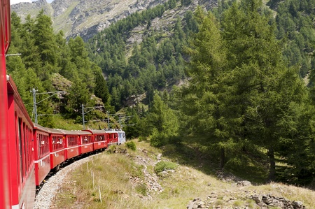 The Bernina Express from Switzerland to Italy.This little red train takes you on one of the 10 greatest train journeys in world.It runs from Tirana in Italy to St Moritz and onto Lake Lugano. It passes glaciers and mountains,ski slopes and Swiss cottages photo