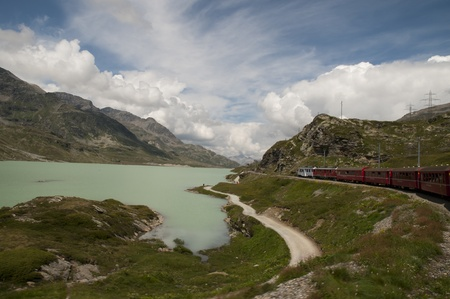 The Bernina Express from Switzerland to Italy. This little red train takes you on one of the 10 greatest train journeys in world. It runs from Tirana in Italy to St Moritz and onto Lake Lugano. It passes glaciers and mountains,ski slopes and Swiss cottage photo