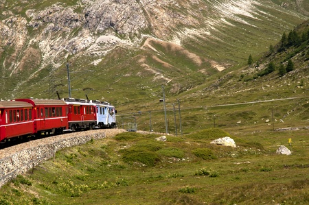The Bernina Express from Switzerland to Italy. This little red train takes you on one of the 10 greatest train journeys in world. It runs from Tirana in Italy to St Moritz and onto Lake Lugano. It passes glaciers and mountains, ski slopes and Swiss cottag photo