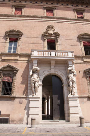 university fountain: Building with Giants guarding the entrance in the Beautiful City of Bologna Italy