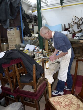 Master Upholsterer working on a late Victorian Chair in Burnley Lancashire Stock Photo - 14543957