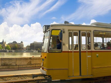 Tram going along the side of the River Danube in Budapest Hungary