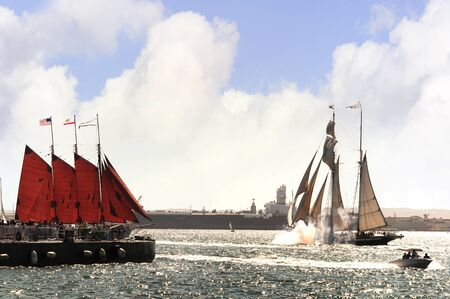Cannons firing in mock sea battle with Tall Sailing Ships in Harbour of San Diego California USA Stock Photo