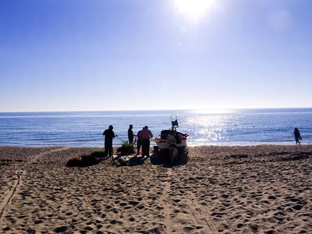 Fishermen sorting out their nets on the Burriana Beach in Nerja Spain photo