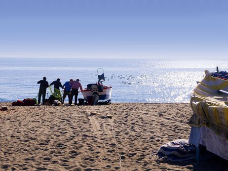 Fishermen sorting out their nets on the Burriana Beach in Nerja Spain Stock Photo - 17562423