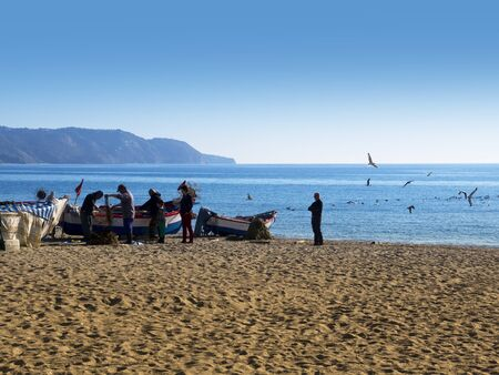 Fishermen sorting out their nets on the Burriana Beach in Nerja Spain