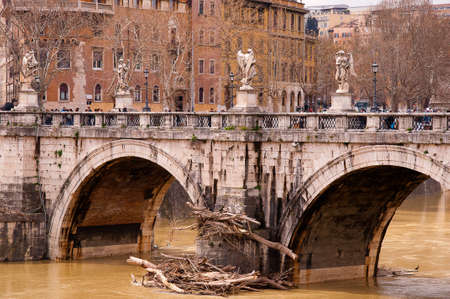 the Castel Sant Angelo Bridge in Rome Italy with debris from the flooded Tiber