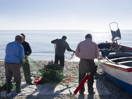 burriana beach: Fishermen sorting out their nets on the Burriana Beach in Nerja Spain
