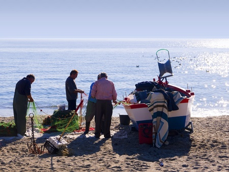sorting out: Fishermen sorting out their nets on the Burriana Beach in Nerja Spain