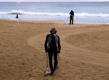 detecting: metal detecting on the beach in Benidorm Spain