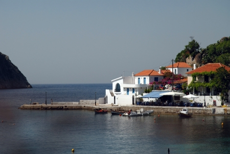 View of the village of Assos on the Island of Kefalonia under pine trees with blue sea and sky
