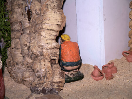 The figure of a Squatting Man, the rebel in the Christmas Crib scene in Nerja Spain