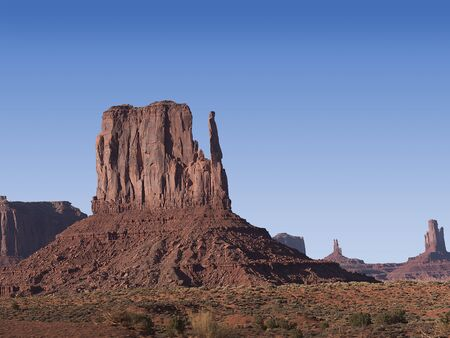 definitive: Monument Valley proporciona quiz�s las im�genes m�s duraderas y definitivas del oeste americano. Las mesas y las motas rojas aisladas est�n rodeadas de un desierto vac�o y arenoso Foto de archivo