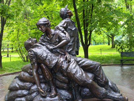 tending: Vietnam Womens Memorial, a sculpture of two women in uniform tending to the wounds of a male soldier while a third woman kneels nearby
