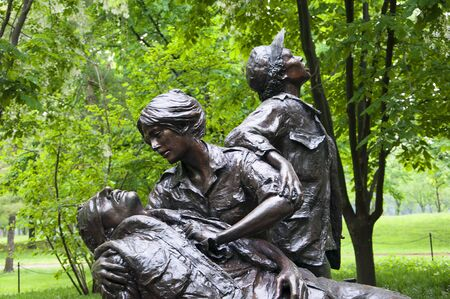 tending: Vietnam Womens Memorial, a sculpture of two women in uniform tending to the wounds of a male soldier while a third woman kneels nearby.
