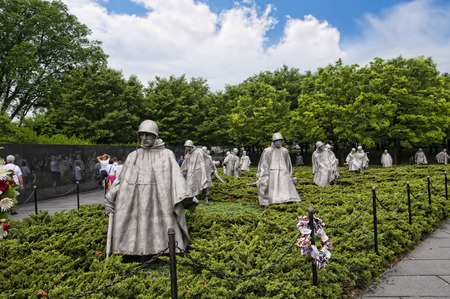"""朝鲜长城纪念碑上有19个雕像,描绘了巡逻士兵的形象。一座花岗岩墙壁上有一幅壁画,上面画着2400名无名士兵的脸,上面写着""""自由不是自由""""。"""