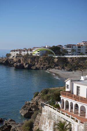 balcon: Paraglider from the Balcon de Europa is a viewpoint down the coast set in the cliffs in Nerja Spain