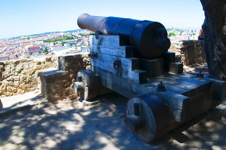 commanding: Cannon at Sao Jorge Castle which is a Moorish castle occupying a commanding hilltop overlooking the historic centre of the Portuguese city of Lisbon and Tagus River. Editorial