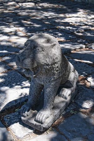 occupying: Stone Lion in Sao Jorge Castle which is a Moorish castle occupying a commanding hilltop overlooking the historic centre of the Portuguese city of Lisbon and Tagus River.