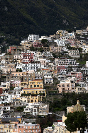 steinbeck: Positano is very original; its buildings cling, in tiers to the rock face. The small houses, all huddling on top of each other form the subject of endless photos. Stock Photo