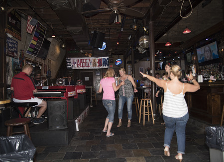 revellers: Revellers at Bar in the French Quarter New Orleans a Louisiana city on the Mississippi River, near the Gulf of Mexico.