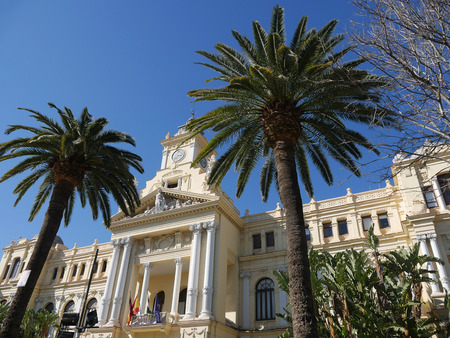 Beautiful Malaga City Hall is surrounded with palm trees full of bright green parakeets presumably from North Africa Editorial