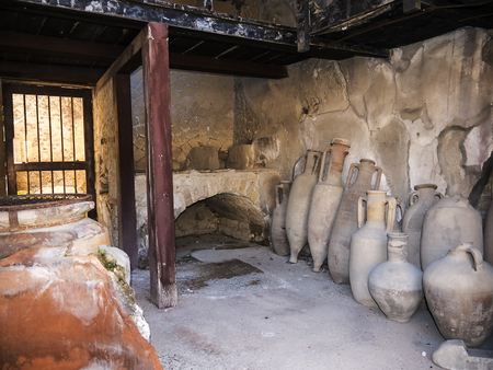 Wine shop in Herculaneum, or Ercolana, near Naples in Italy was not buried by falling rocks like Pompeii was in the eruption of Vesuvius in 79AD, instead it was engulfed in boiling mud and superheated air. Banco de Imagens - 110649903