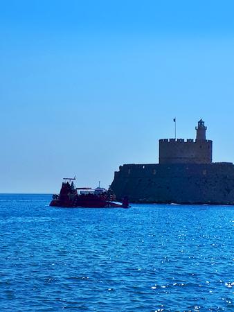 Boat leaving Mandraki Harbour on the island of Rhodes