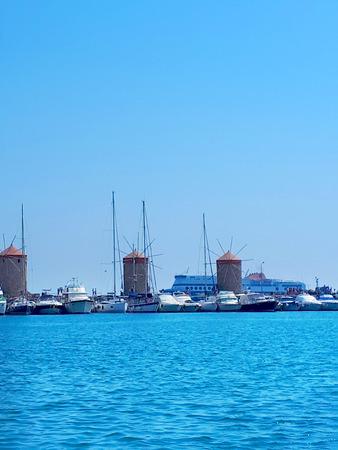 These 3 windmills stand on the Mandraki harbor wall with the fort of St Nikolas in the distance on the Greek island Of Rhodes.