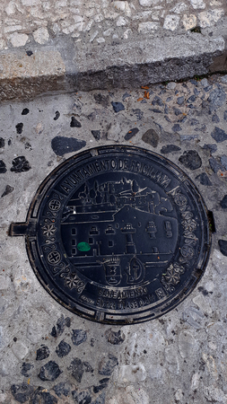 Drain cover in Frigiliana with the  the old sugar factory of the village no defunct Editorial