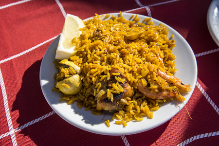 Plate of paella cooked on a wood burning fire on the Burriana beach in Nerja Spain Stock Photo