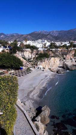 The Carabeo beach with a fishermans hut tucked in the cliffs viewed from the Balcon de Europa in Nerja Spain