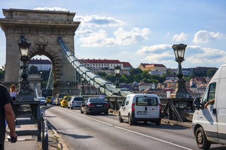 The iconic Chain Bridge in Budapest Hungary that carries traffic across the River Danube in the Baroque city of Budapest.. Designed by English Engineer William Tierney Clark was the first across the Danube and was opened to traffic in 1849