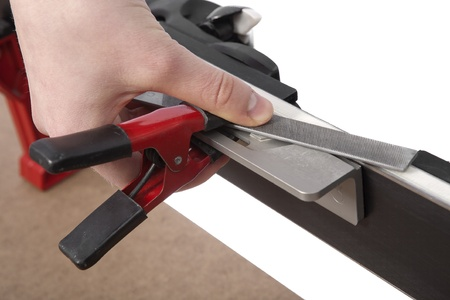filing race ski edge with chrome file held by clamp on bevel guide